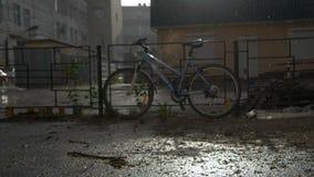 在多雨天气的篱芭附近停放的自行车 股票录像