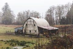 在多雨的冬季风景的老农舍 免版税库存图片