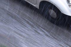 在多雨街道上的模糊的驾驶的汽车细节在行动迷离大角度视图 免版税库存照片