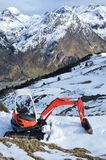 在多雪的倾斜的挖掘机 免版税库存图片