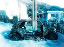 在多雪的停车处的老被烧的汽车 库存照片