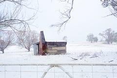在多雪的农村场面的摇晃土气棚子 免版税库存图片