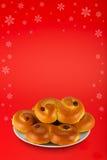 在多雪的圣诞节背景的典型的瑞典番红花小圆面包 免版税库存照片