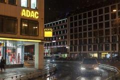 在多雪的夜期间被采取的他们的街市慕尼黑大会办公处的ADAC商标 ADAC是主要汽车俱乐部在德国 免版税图库摄影