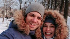 在多雪的天结合谈话在录影连接和走在冬天城市公园的男人和妇女与落的雪 股票录像
