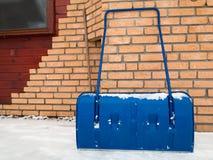在多雪的天,冬时期间,蓝色雪铁锹 免版税图库摄影