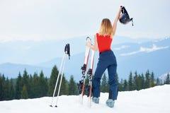 在多雪的小山的上面的女子滑雪者与滑雪的在滑雪胜地 免版税库存照片