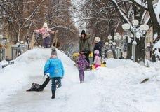 在多雪的小山的儿童喜跳 免版税图库摄影