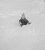 在多雪的小山的愉快的儿童骑马在冬天 库存照片