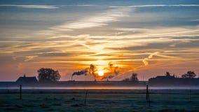 在多雪的小牧场抽烟的烟囱的金黄冬天太阳 免版税图库摄影
