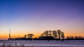 在多雪的小牧场的金黄冬天太阳在农舍和树后 免版税库存图片
