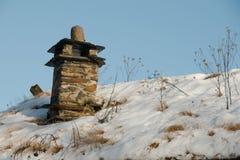 在多雪的屋顶的烟管子 库存照片