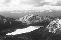 在多雪的山中的冻湖 免版税库存照片