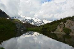在多雪的山前面的湖 图库摄影