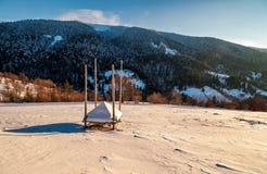 在多雪的山坡流洒的空的干草堆 免版税库存图片