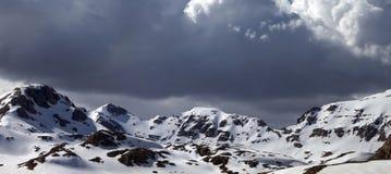 在多雪的山的全景在云彩 库存照片