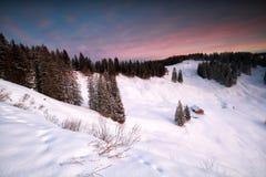 在多雪的山的客舱在日出 免版税图库摄影