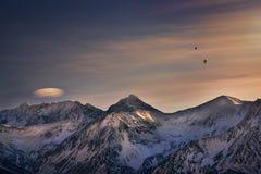 在多雪的山的气球在日落期间 免版税库存图片