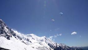 在多雪的山的滑翔伞飞行 反对monblan山的背景的滑翔伞 股票录像