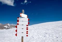 在多雪的山的空白的路标 库存照片