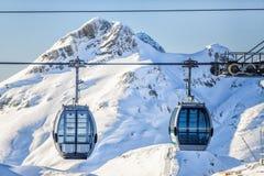 在多雪的山背景的两间空中览绳滑雪电缆车客舱 免版税库存照片