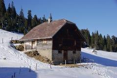 在多雪的山腰的瑞士山中的牧人小屋 库存图片