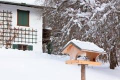 在多雪的房子附近的鸟舍 免版税库存照片