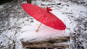 在多雪的日志的红色日本伞 免版税库存图片