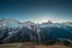 在多雪的日落的山 免版税库存图片