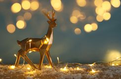 在多雪的木桌上的金发光的驯鹿与圣诞节诗歌选点燃 免版税库存照片