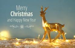 在多雪的木桌上的金发光的驯鹿与圣诞节诗歌选点燃 免版税库存图片