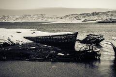 在多雪的海岸附近的凹下去的船在Teriberka,摩尔曼斯克地区,俄罗斯 免版税图库摄影