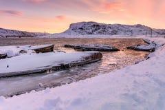 在多雪的海岸附近的凹下去的船在Teriberka,摩尔曼斯克地区,俄罗斯 免版税库存图片