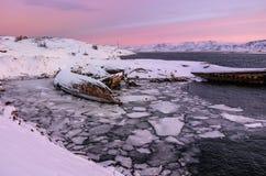 在多雪的海岸附近的凹下去的船在Teriberka,摩尔曼斯克地区,俄罗斯 图库摄影