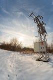 在多雪的草甸中间的电杆 免版税库存图片