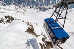 在多雪的谷上的馆山索道与阴影 免版税图库摄影