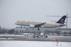 在多雪的跑道的沙乌地阿拉伯航空空中客车A320-200 HZ-ASB着陆 图库摄影