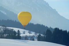 在多雪的阿尔卑斯上的黄色气球在Kaiserwinkl奥地利 库存照片