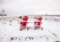 在多雪的领域的两把红色阿迪朗达克椅子 免版税库存照片