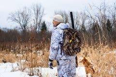 在多雪的领域的猎人 免版税库存照片