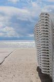 在多暴风雨的天气期间, Sunbeds在海滩堆积了 库存照片