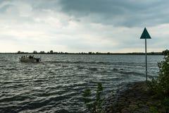 在多暴风雨的天气的小游艇在荷兰河 免版税图库摄影