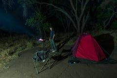 在夜之前供以人员烹调与火木头和braai设备 帐篷和椅子在前景 冒险在非洲国家公园 库存图片