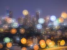 在夜光风景的被弄脏的bokeh图象在城市 免版税库存照片