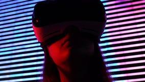 在夜城市光的妇女佩带的vr耳机,被模仿的环境,赌博 影视素材