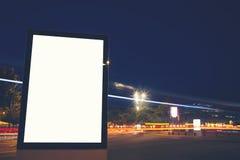 在夜城市的奔忙的街道上的现代广告牌 免版税库存图片