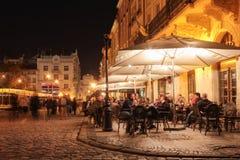 在夜城市的老街道上的街道咖啡馆 图库摄影