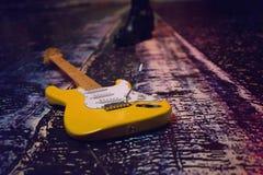 在夜城市的背景的典雅的黄色吉他 免版税库存图片