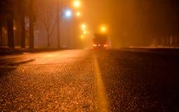 在夜城市的街道上的雾 柏油路和汽车在雾 湿沥青,在冬天季节的危险溜滑路 Stre 库存照片