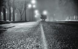 在夜城市的街道上的雾 柏油路和汽车在雾 湿沥青,在冬天季节的危险溜滑路 Stre 免版税库存图片